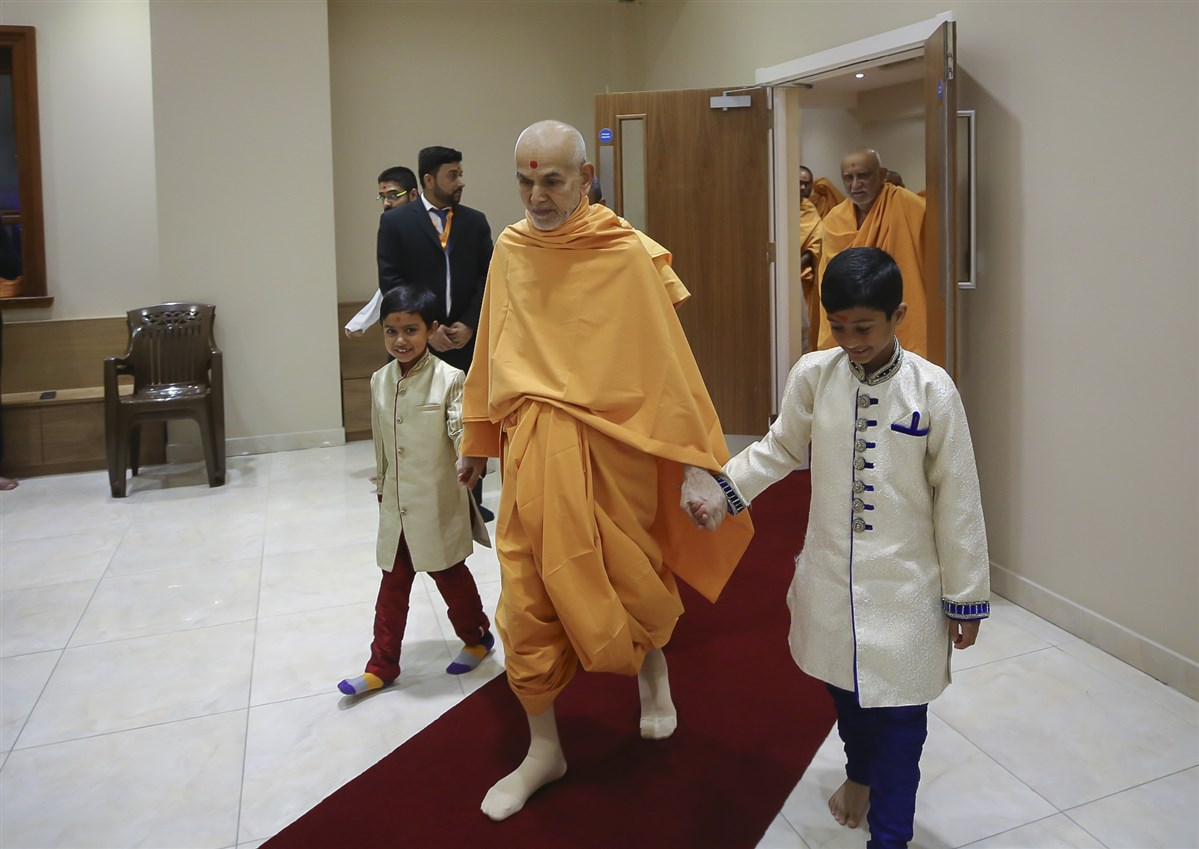 Param Pujya Mahant Swami Maharaj makes his way to the abhishek mandap, led by two balaks