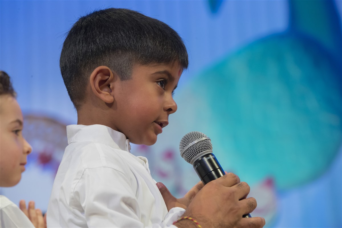A child recites scriptural passages during Swamishri's puja