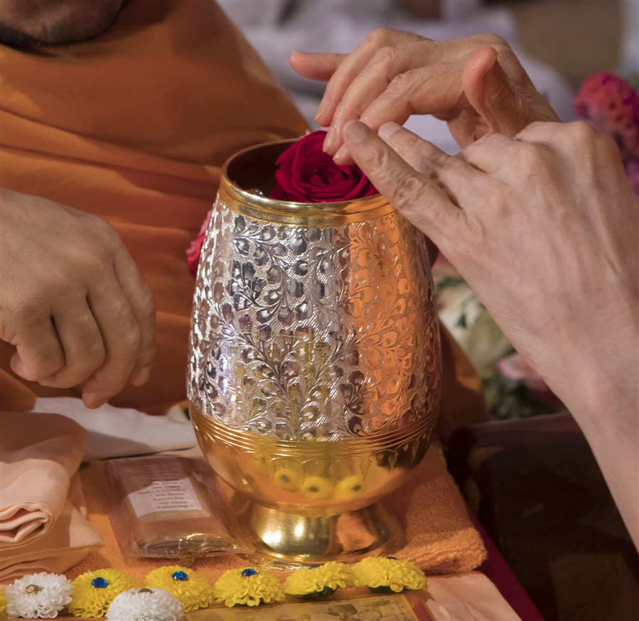 Swamishri sanctifies water with roses used in his puja