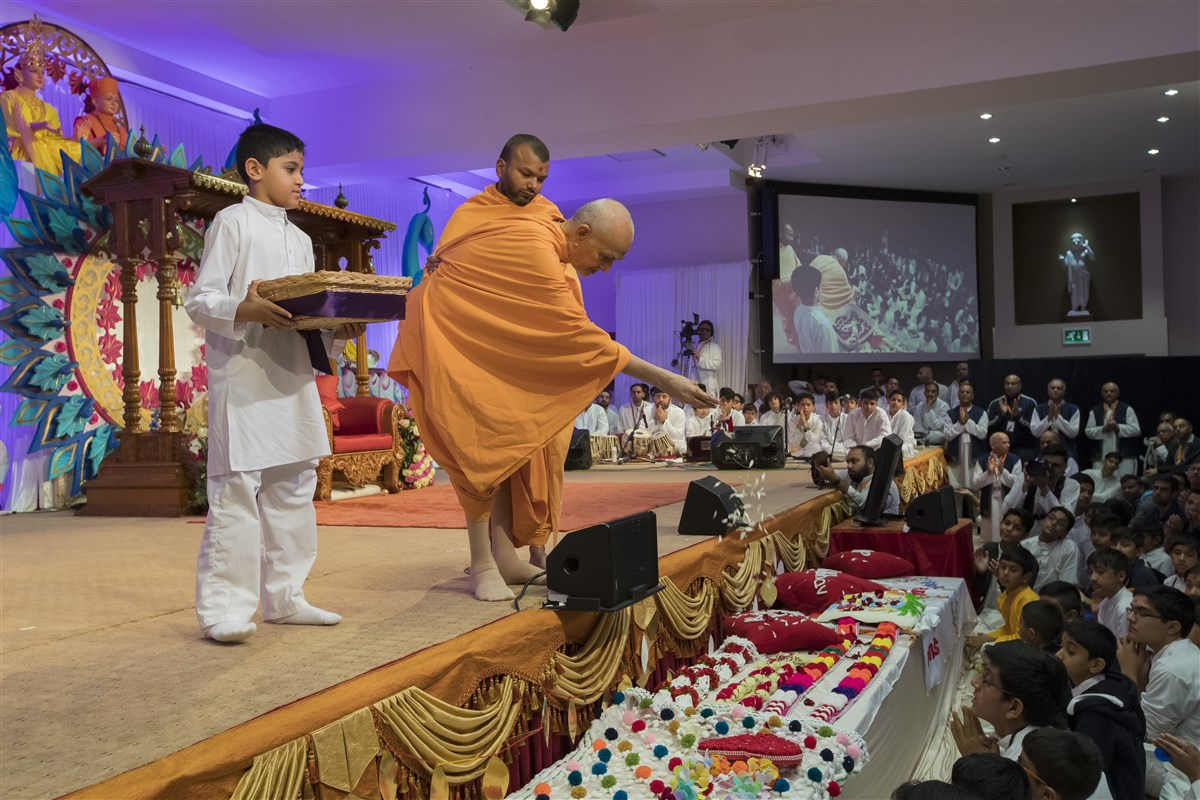 Swamishri sanctifies various devotional offerings with flower petals
