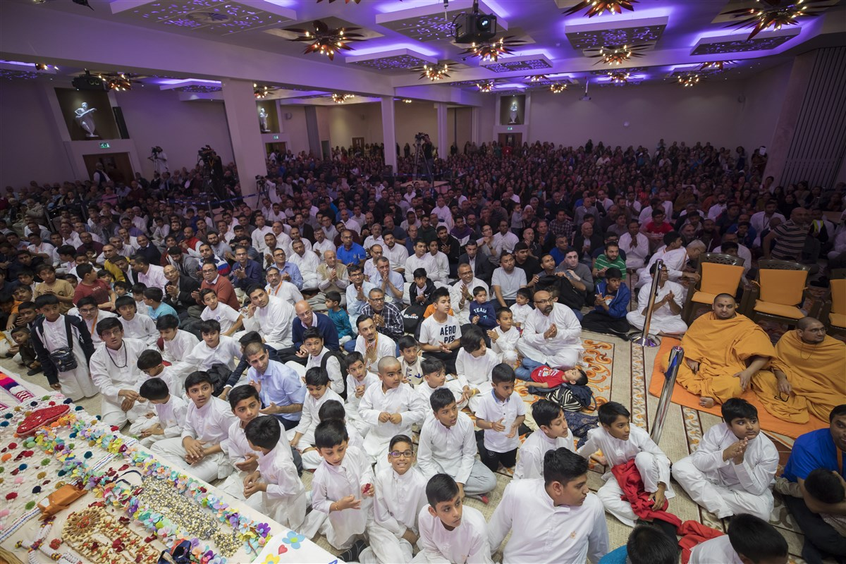 Devotees engrossed in Swamishri's darshan as he departs the hall