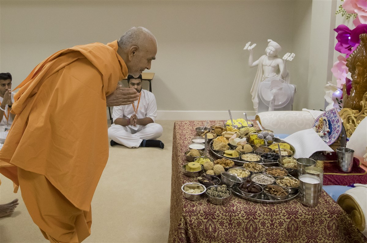 Swamishri engrossed in the darshan of Shri Harikrishna Maharaj accepting thal
