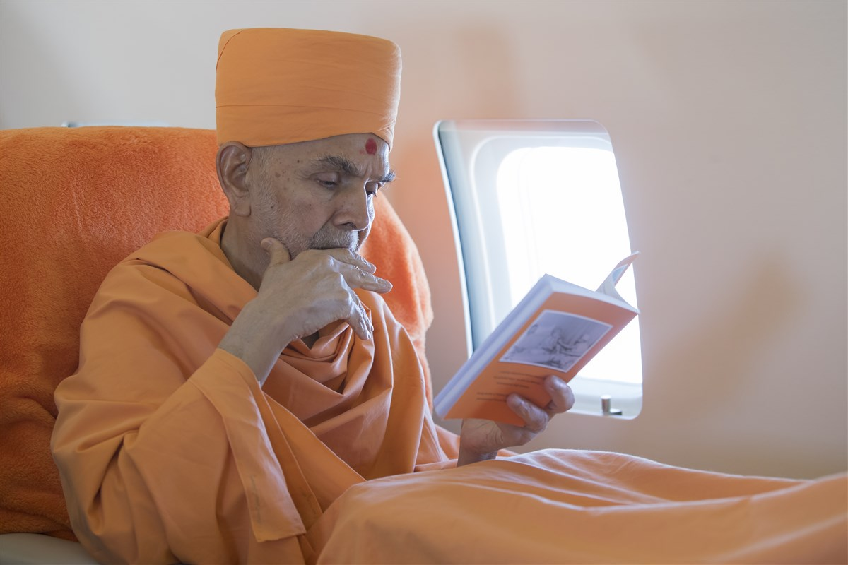 Even before take-off, Swamishri is engrossed in a book