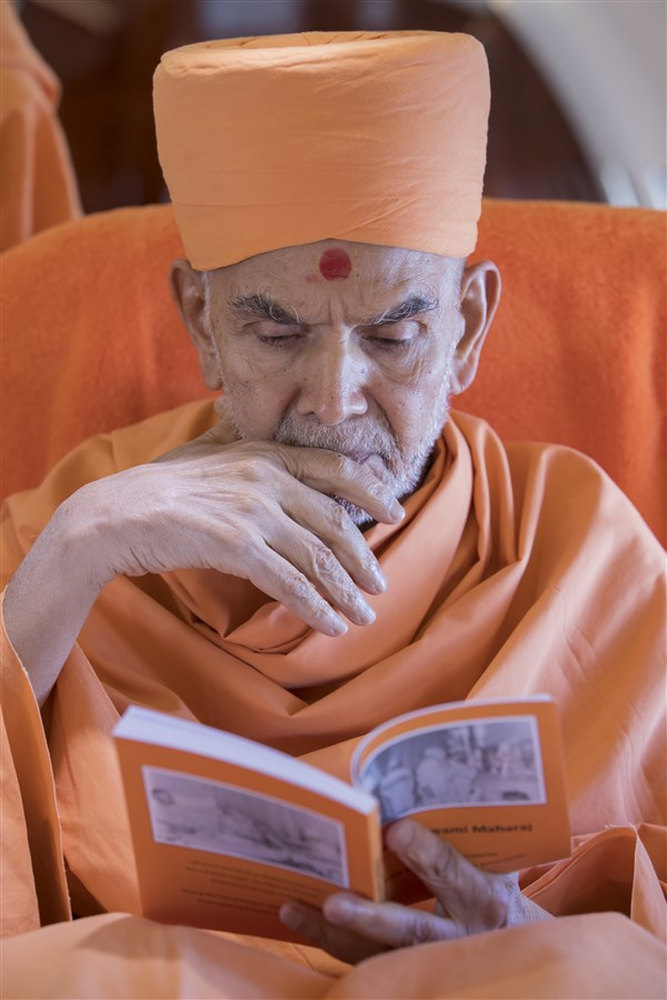 Swamishri is reading a forthcoming publication, comprising excerpts from Yogiji Maharaj's extensive jivancharitra