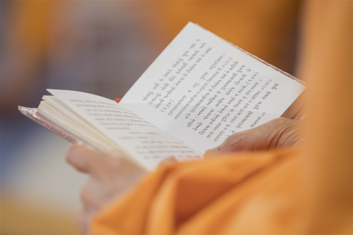 Swamishri reads the Shikshapatri in conclusion to his puja