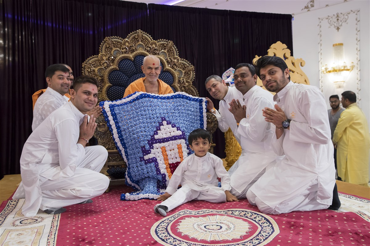 Volunteers from France honour Swamishri with a shawl crafted from satin flowers