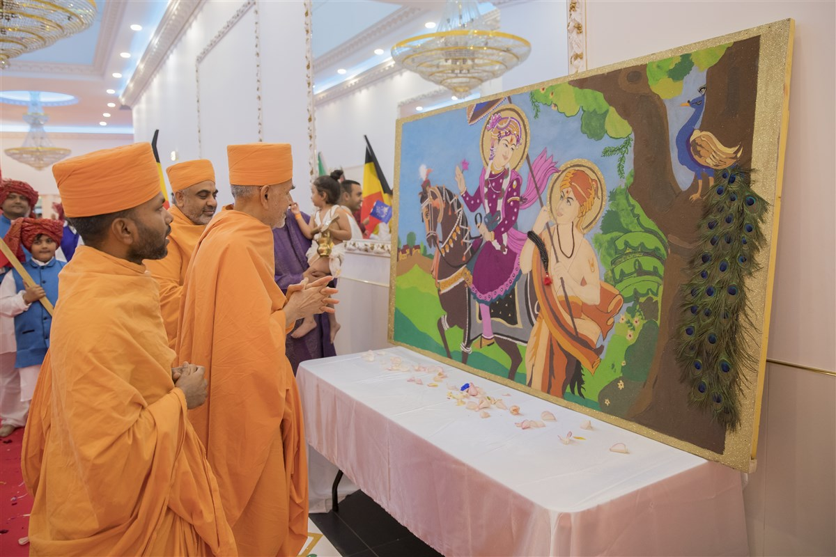 Swamishri observes a piece of devotional art