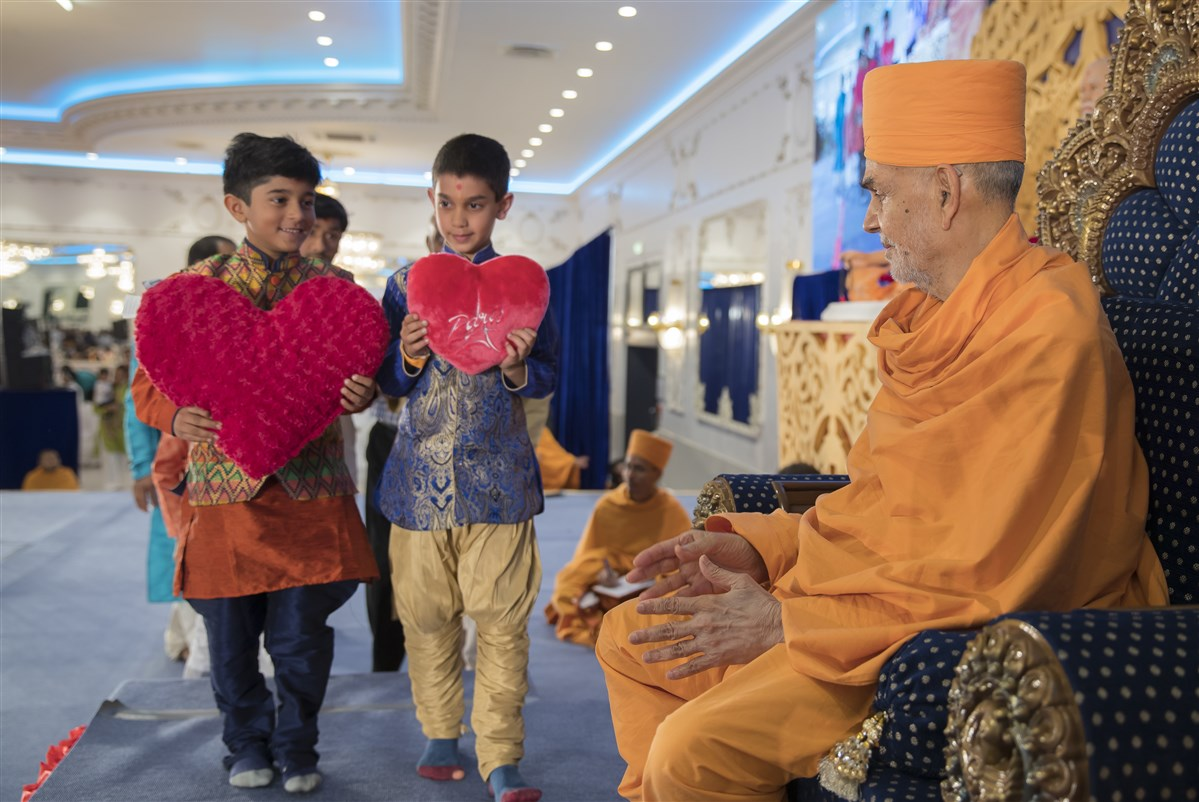 Children from France offer Swamishri heart-shaped velvet cushions, symbolic of the devotees' loving devotion