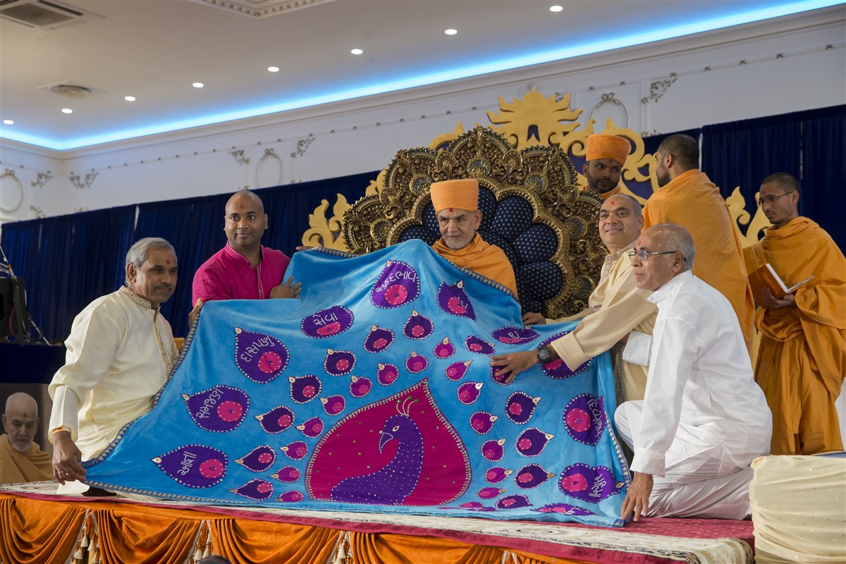 Devotees from Italy honour Swamishri with a decorative shawl