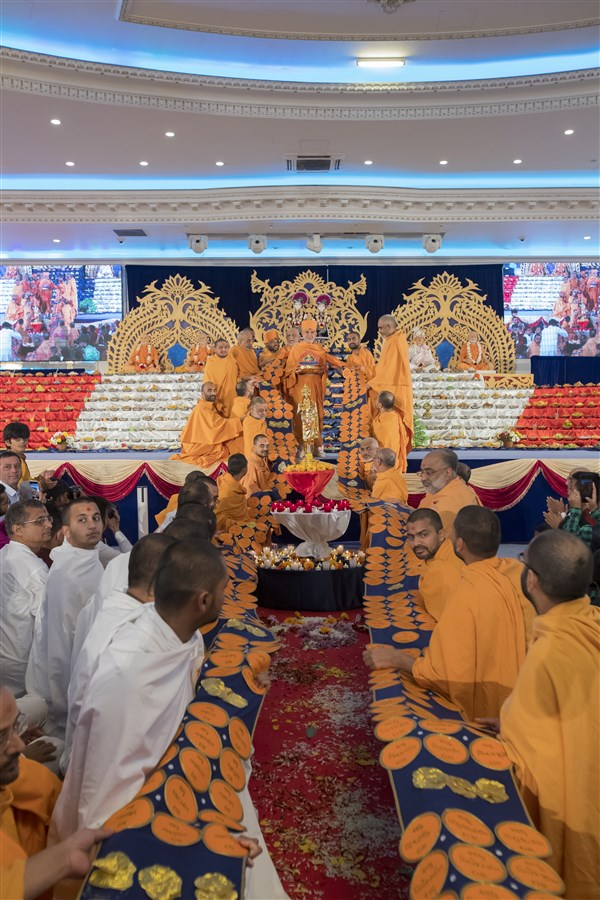 Swamis honour Swamishri with a decorative garland inscribed with the name of every BAPS swami - over a thousand