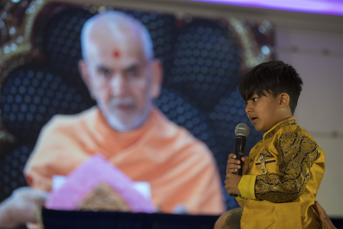 A child from Paris recites a Vachanamrut during Swamishri's puja