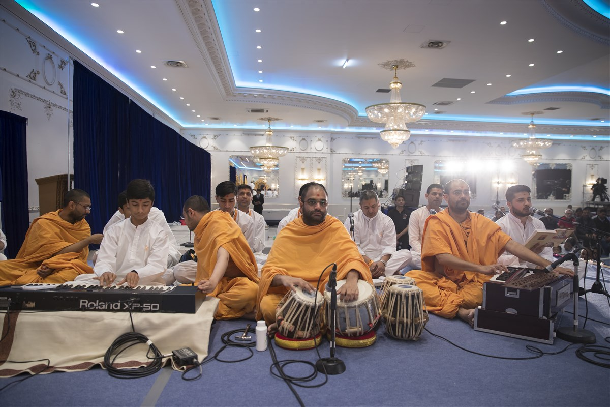 Devotees sing kirtans during Swamishri's puja