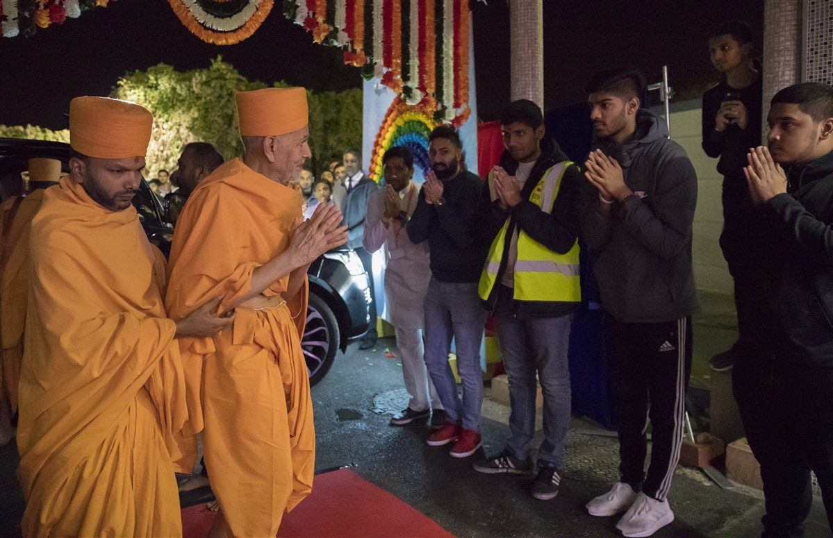 Param Pujya Mahant Swami Maharaj greets volunteers with folded hands as he arrives for his morning puja