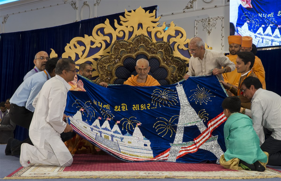 Devotees from Europe honour Swamishri with a decorative shawl