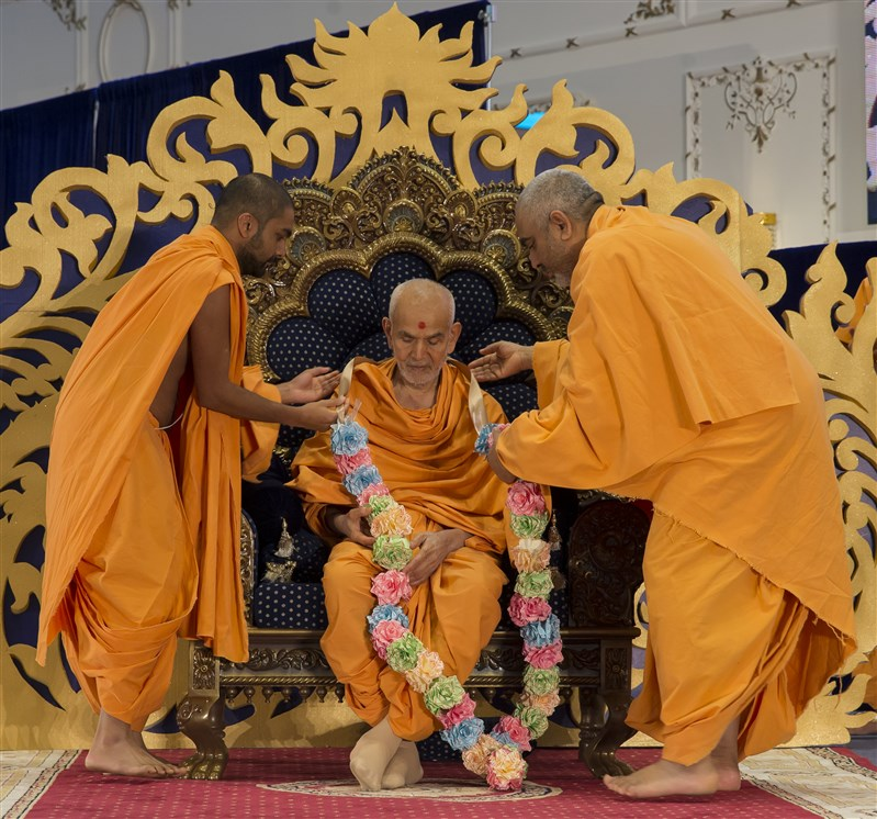 Yogvivekdas Swami and Paramsevadas Swami honour Swamishri with a decorative garland