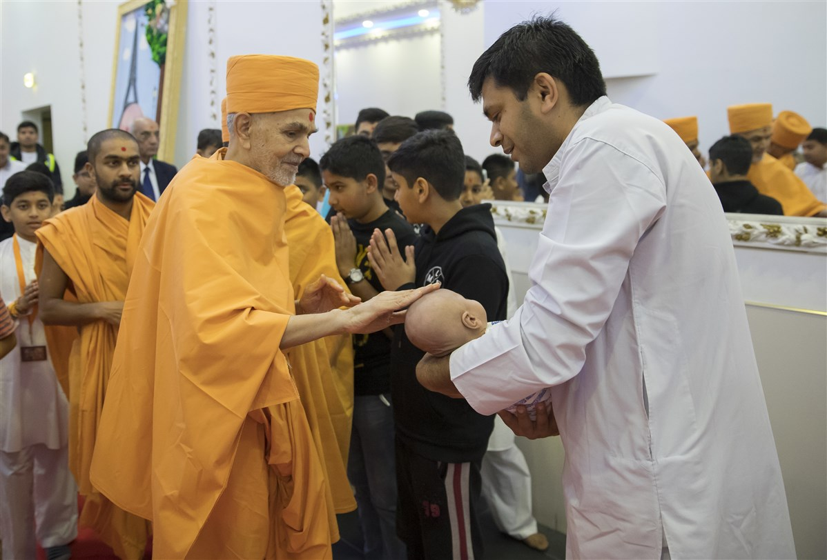 Swamishri blesses a young child