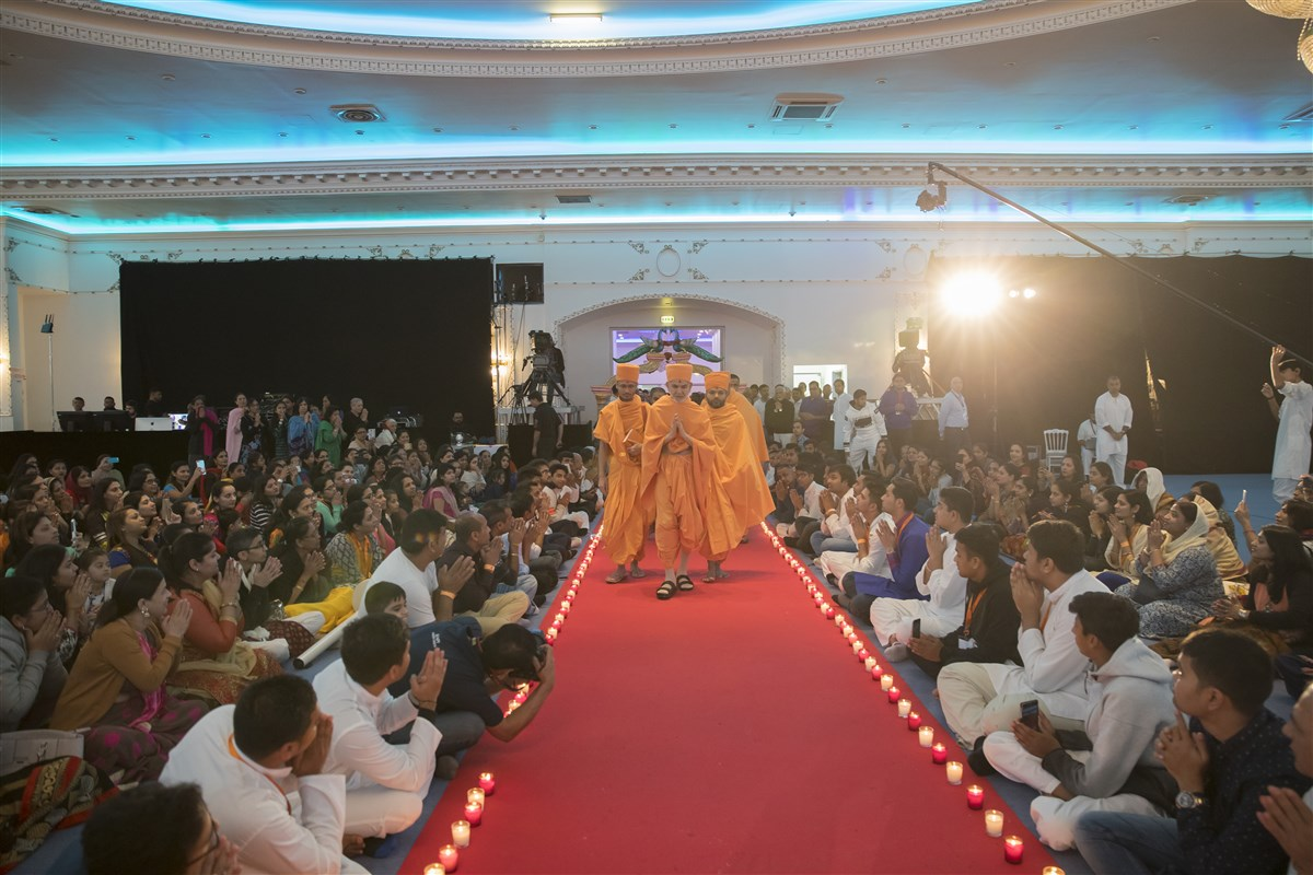 Swamishri arrives in the assembly hall, his path lined by divas in celebration of the festive Diwali period