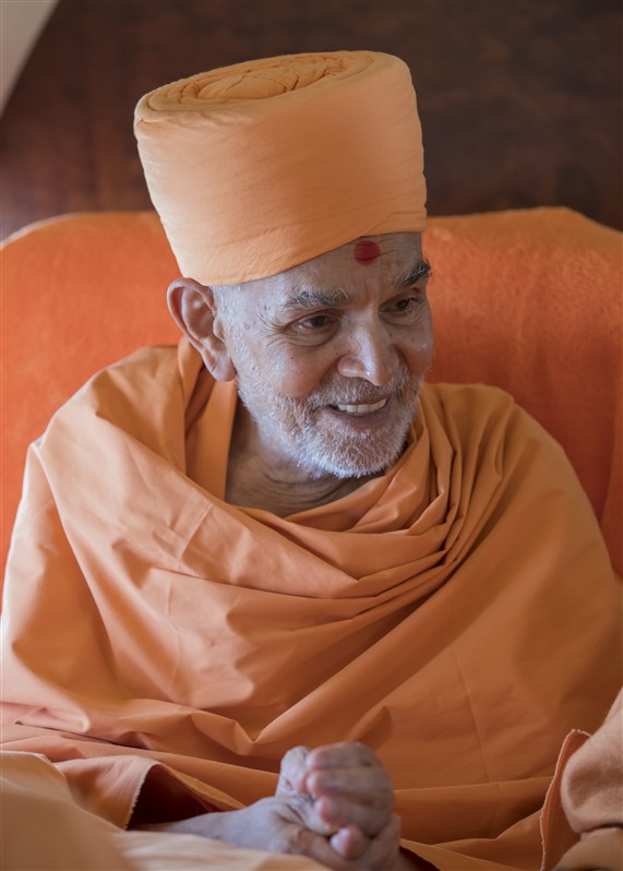 Swamishri engaged in conversation during the journey