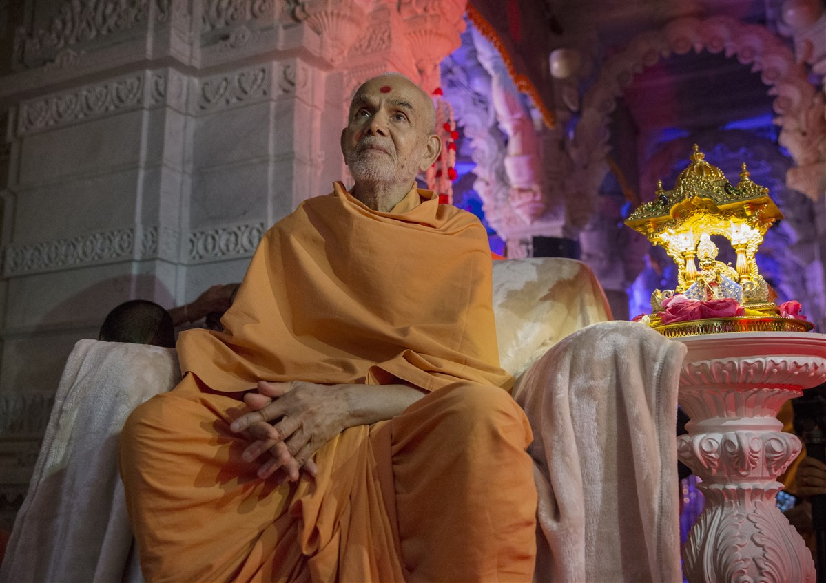 Swamishri observes the fireworks display with Shri Harikrishna Maharaj from inside the mandir sanctum