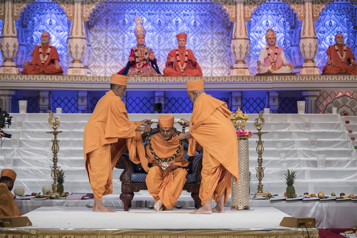 Narayanmunidas Swami and Atmaswarupdas Swami honour Swamishri with a decorative garland