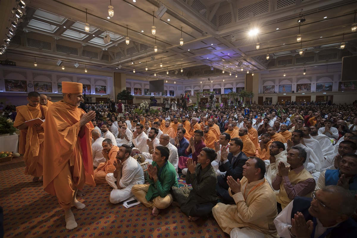 Swamishri departs the annakut assembly with folded hands