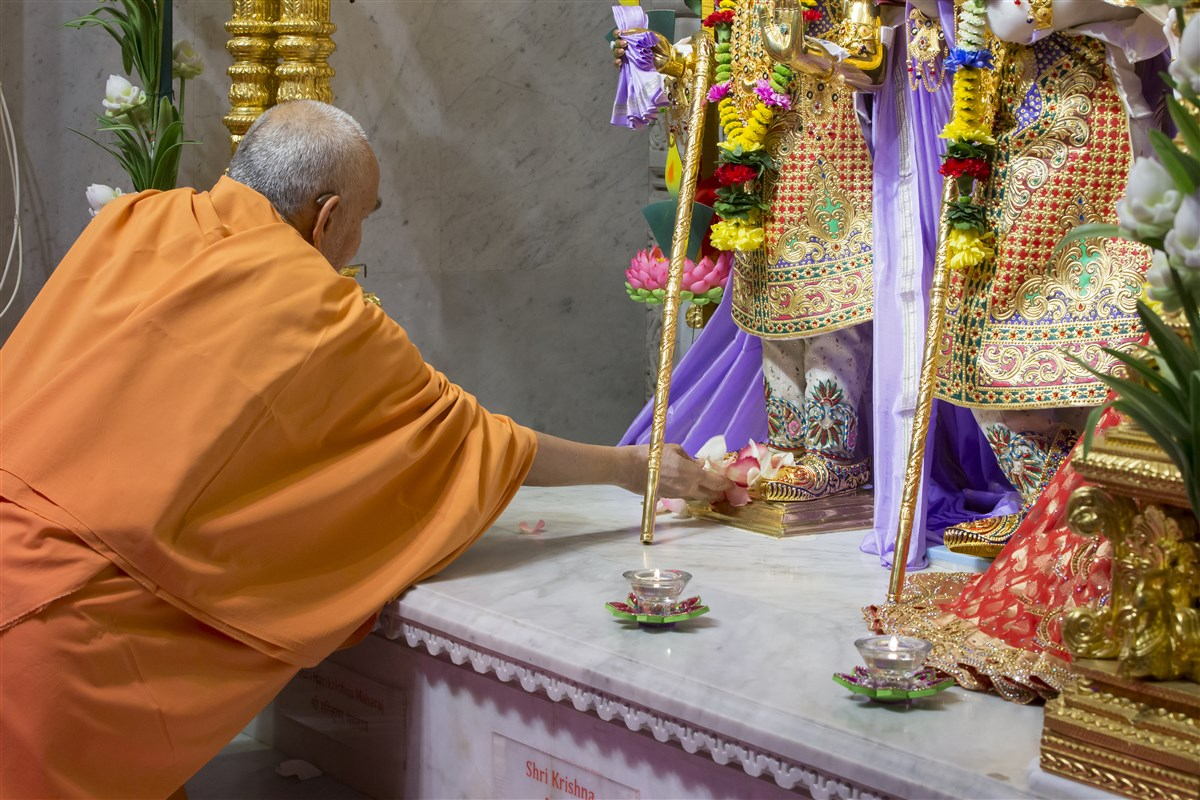 Swamishri places flower petals at the feet of Shri Harikrishna Maharaj