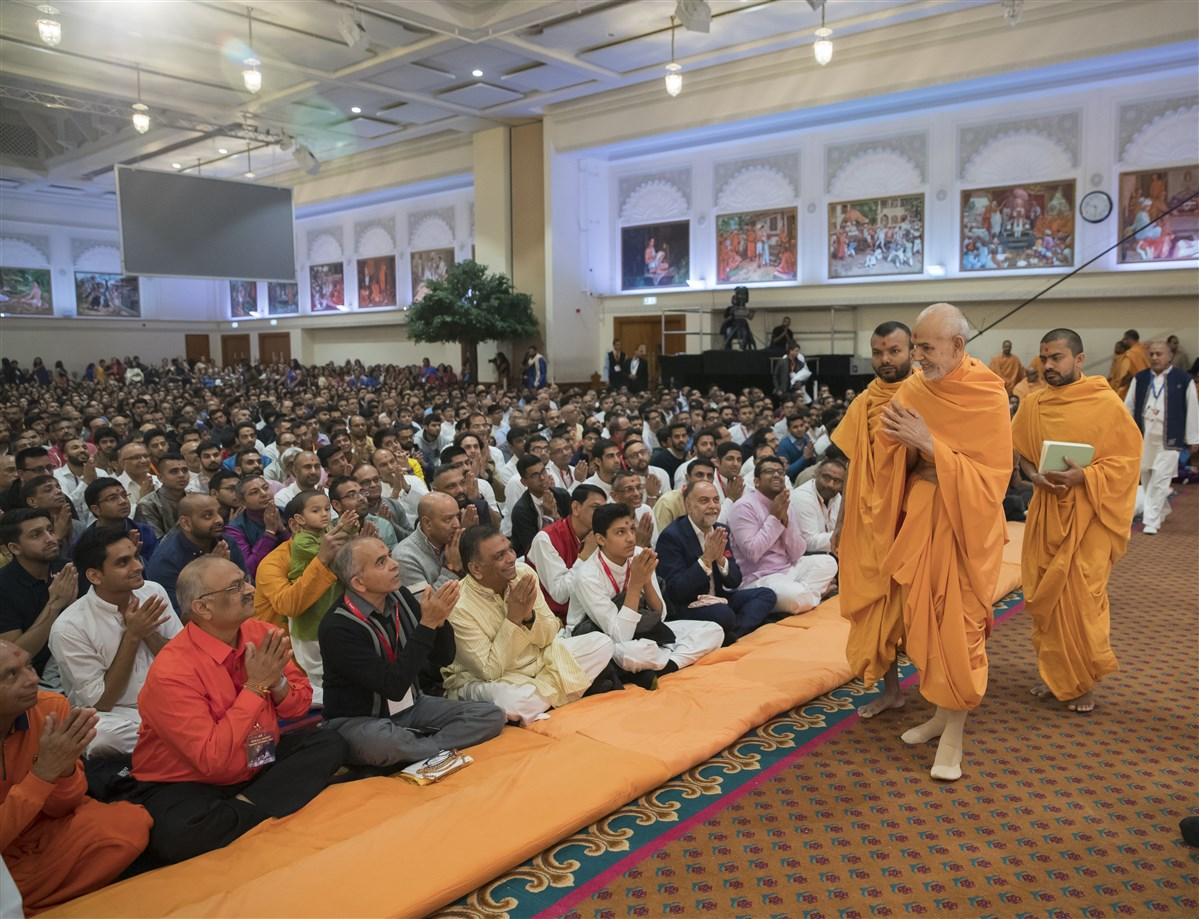 Swamishri arrives in the assembly hall greeting devotees with folded hands