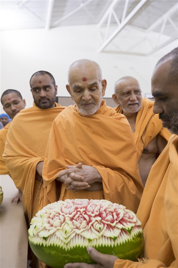 Swamishri observes an intricately carved watermelon for the annakut