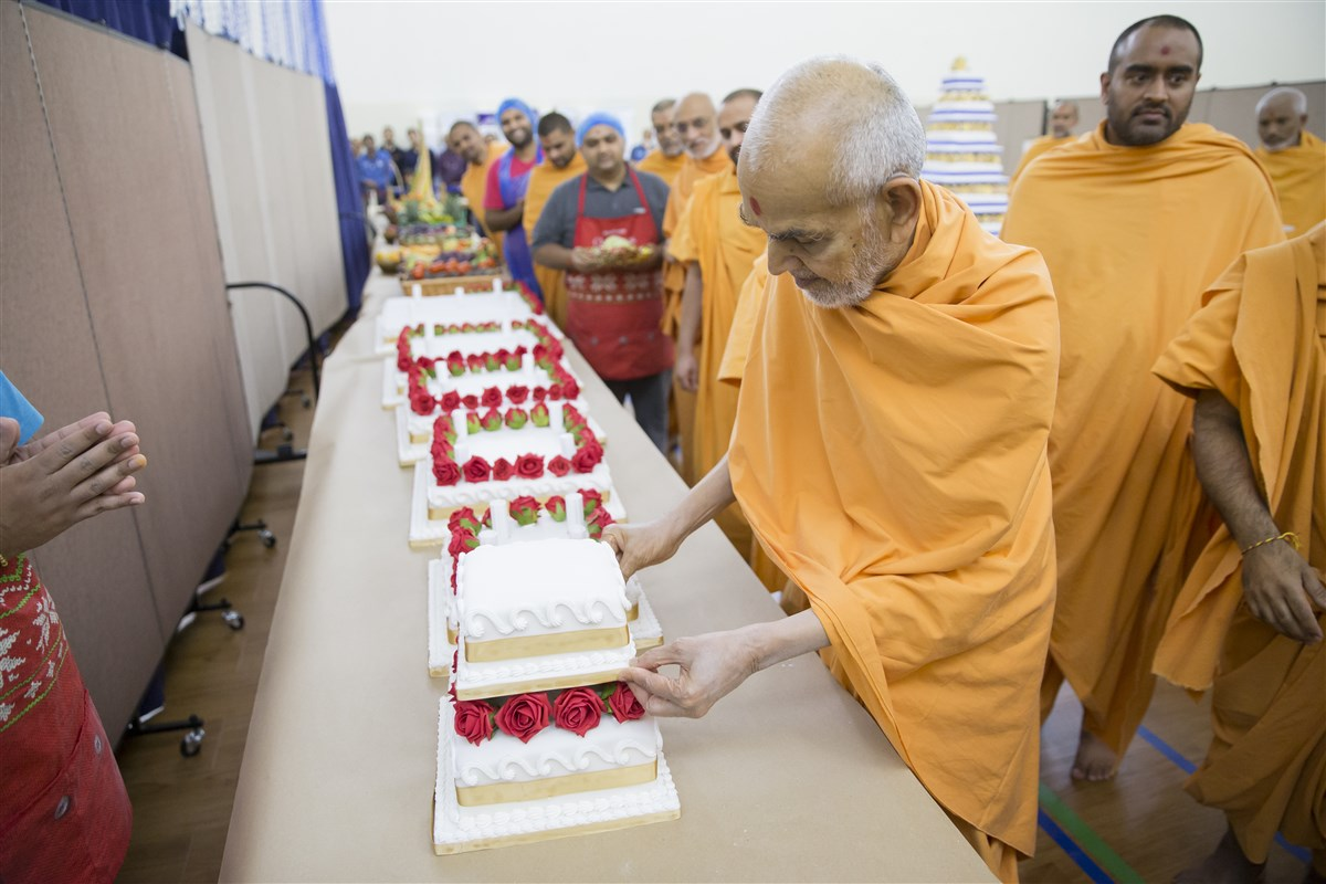 Swamishri helps assemble a multi-tier cake for the annakut