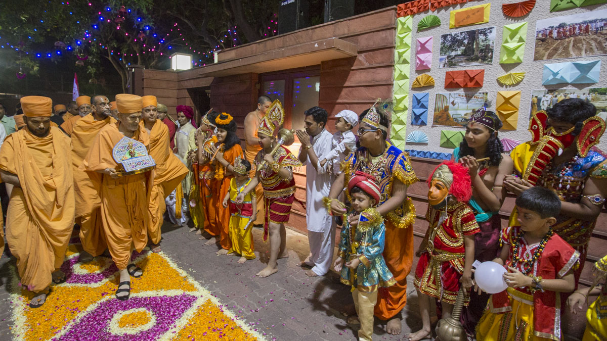 Children in traditional costumes welcome Swamishri
