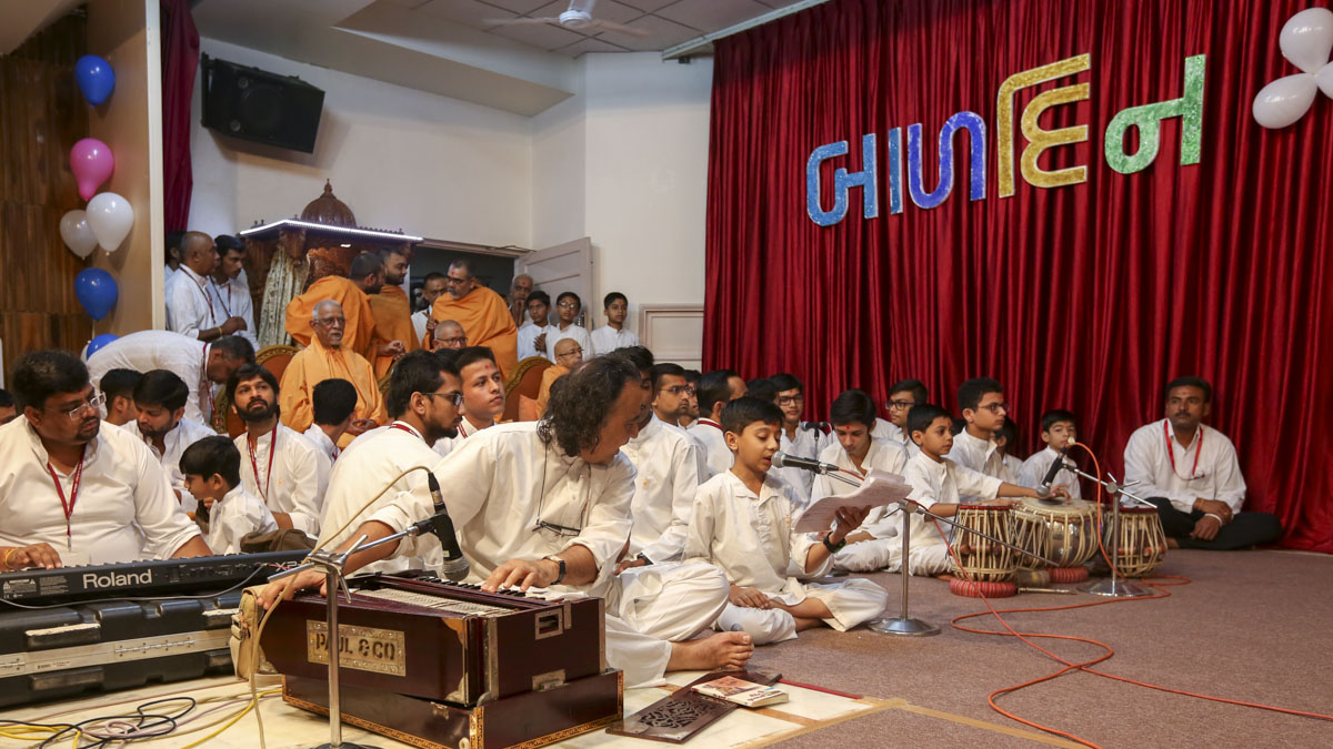 Children sing kirtans in Swamishri's puja