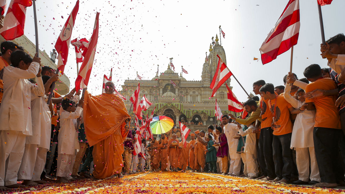 Devotees with BAPS flags welcome Swamishri