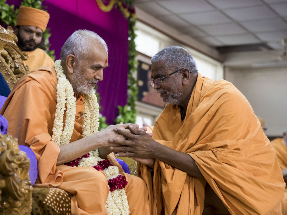 Vedagna Swami welcomes Swamishri with a garland