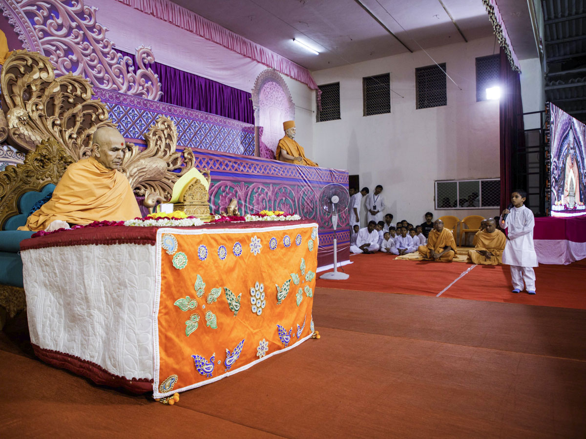 A child presents in Swamishri's morning puja