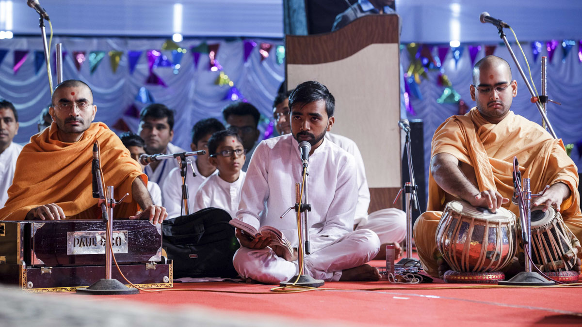 A youth sings a kirtan in Swamishri's puja
