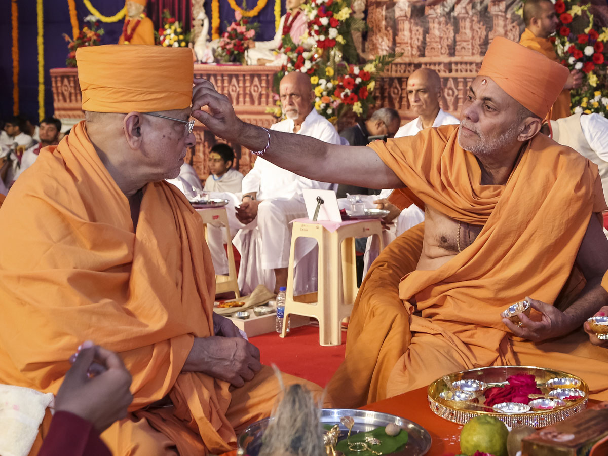 Pujya Viveksagar Swami applies chandlo to Pujya Ishwarcharan Swami