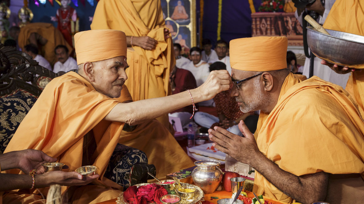 Swamishri applies chandlo to Abhayswarup Swami