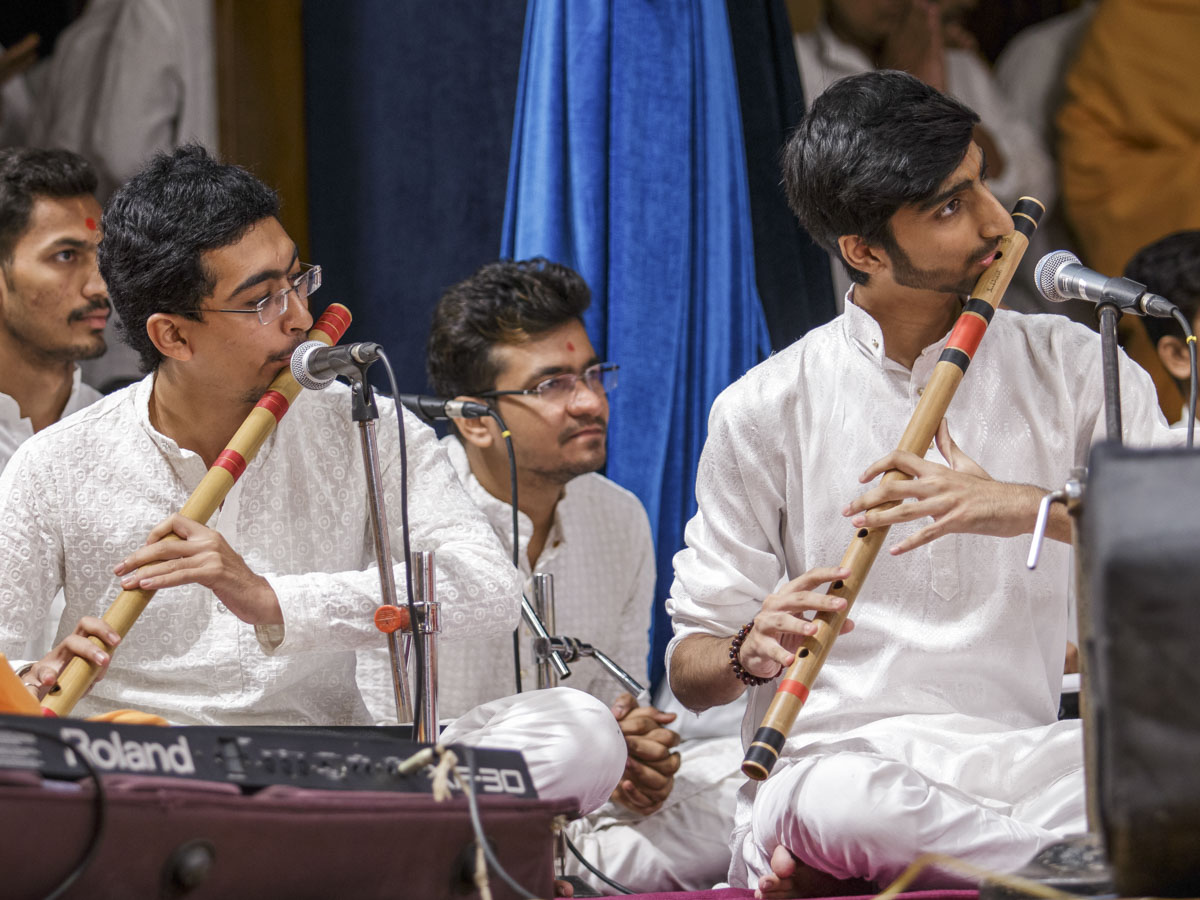 Youths play flutes in Swamishri's puja