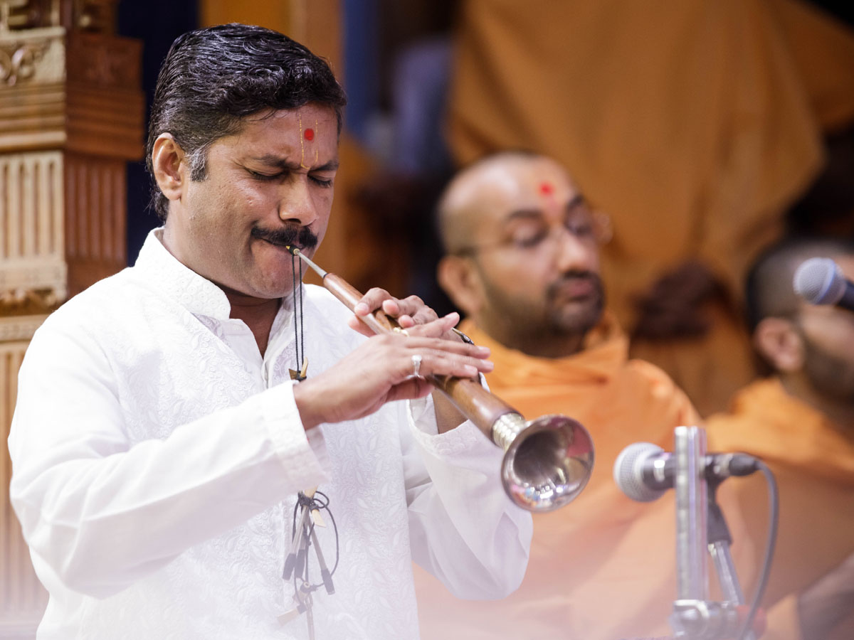 A devotee plays the shehnai in Swamishri's puja