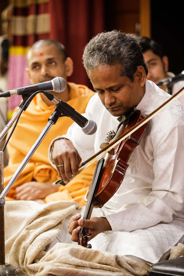 An artiste plays the violin in Swamishri's puja