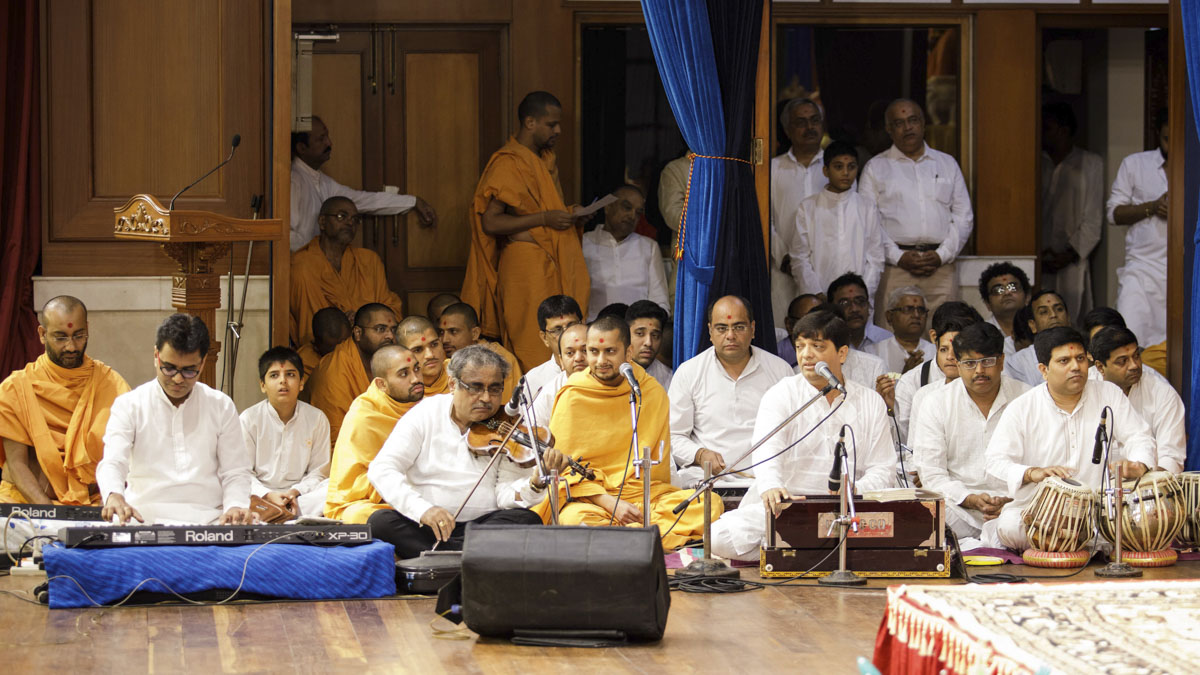 Sadhus and devotees sing kirtans in Swamishri's puja