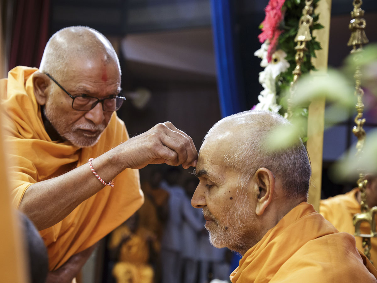 Pujya Kothari Swami applies chandlo to Swamishri