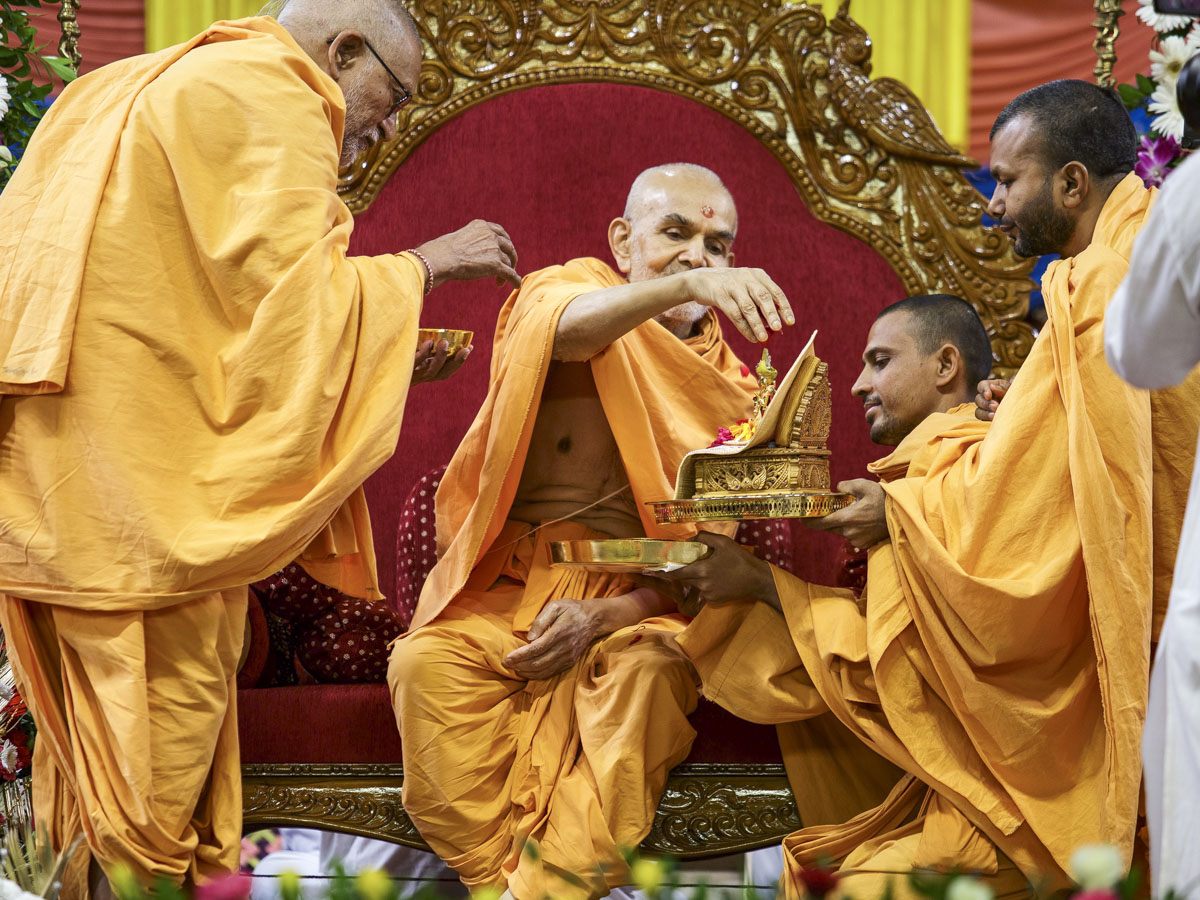 Swamishri showers flower petals on Shri Harikrishna Maharaj in the Bhakti Din assembly