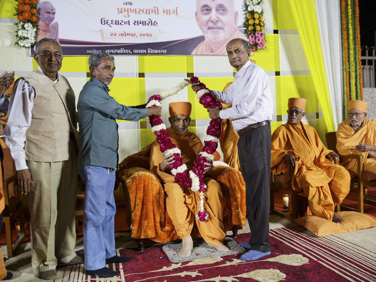 President and Vice-President of Vidyanagar Nagarpalika honor Swamishri, with a garland