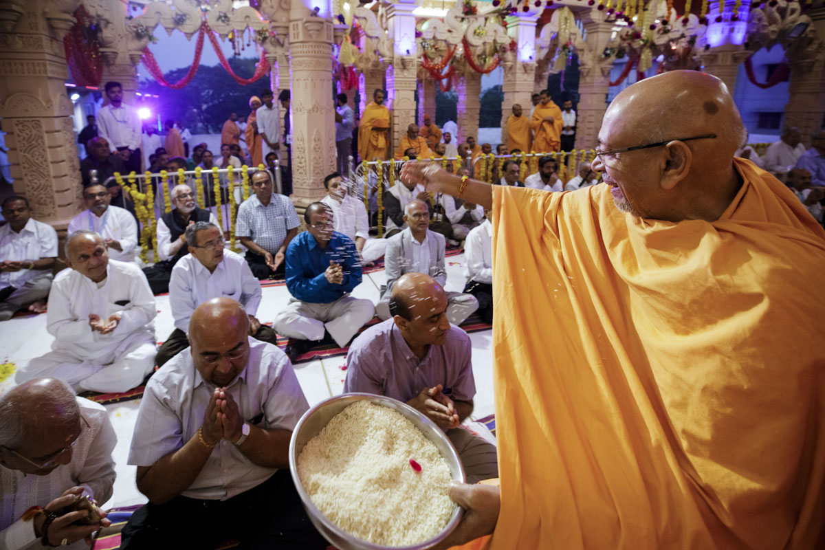 Pujya Tyagvallabh Swami blesses devotees by showering rice grains
