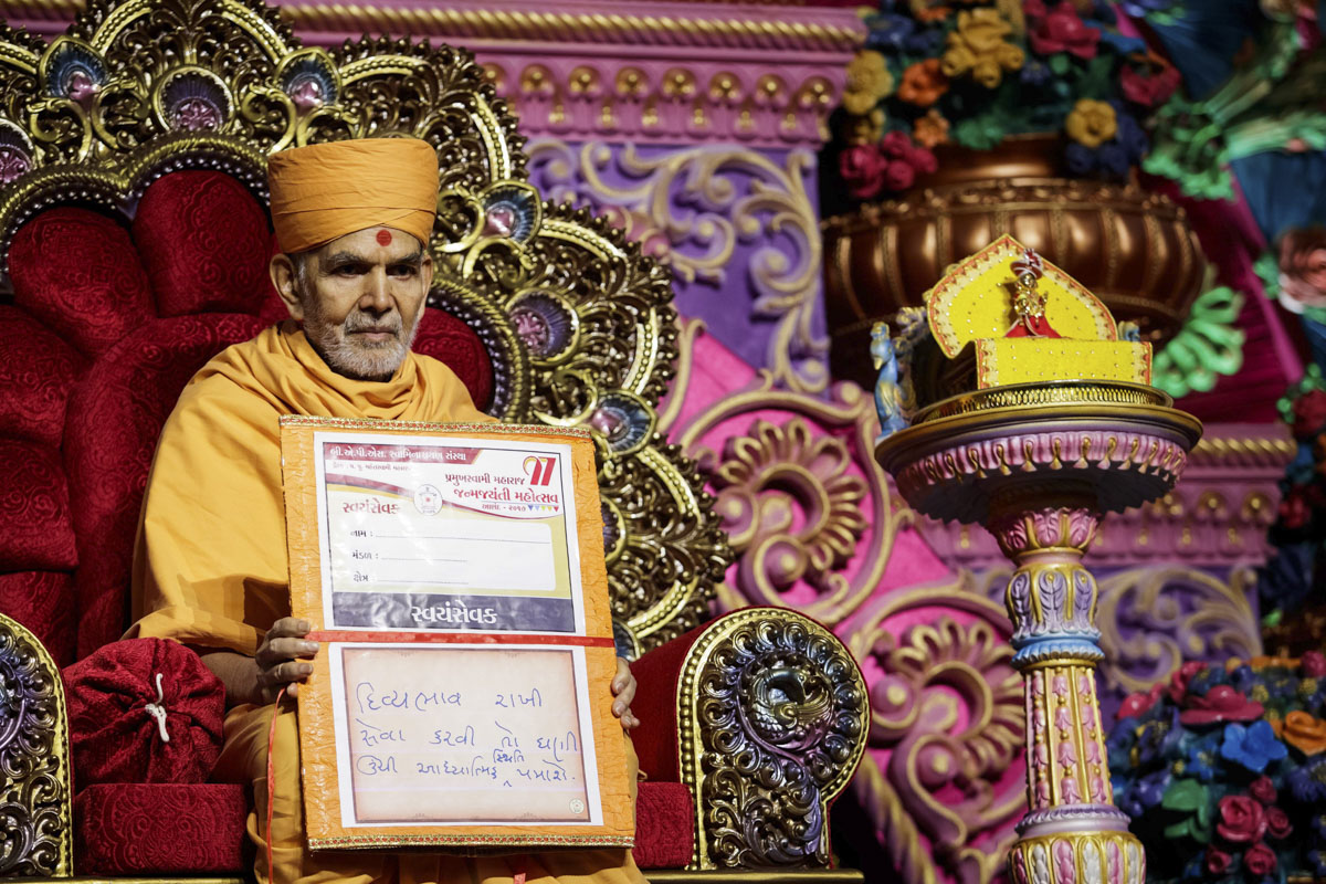 Swamishri sanctifies a large version of the ID card for volunteers