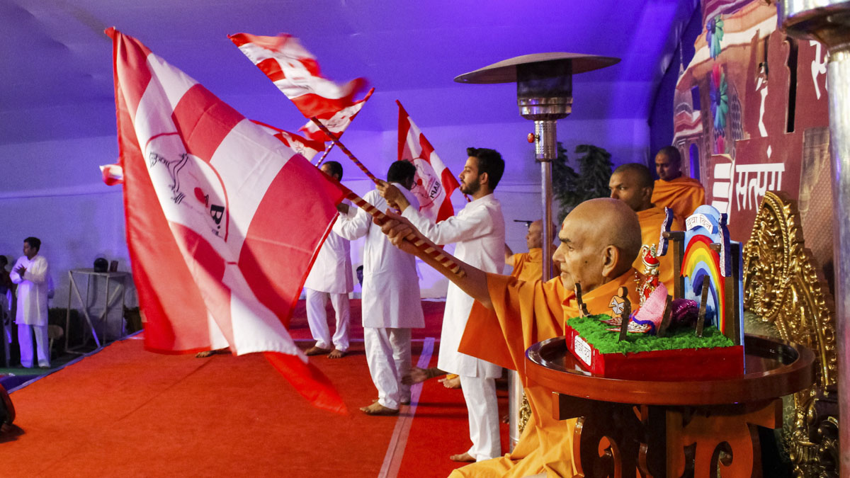 Swamishri and youths wave BAPS flags