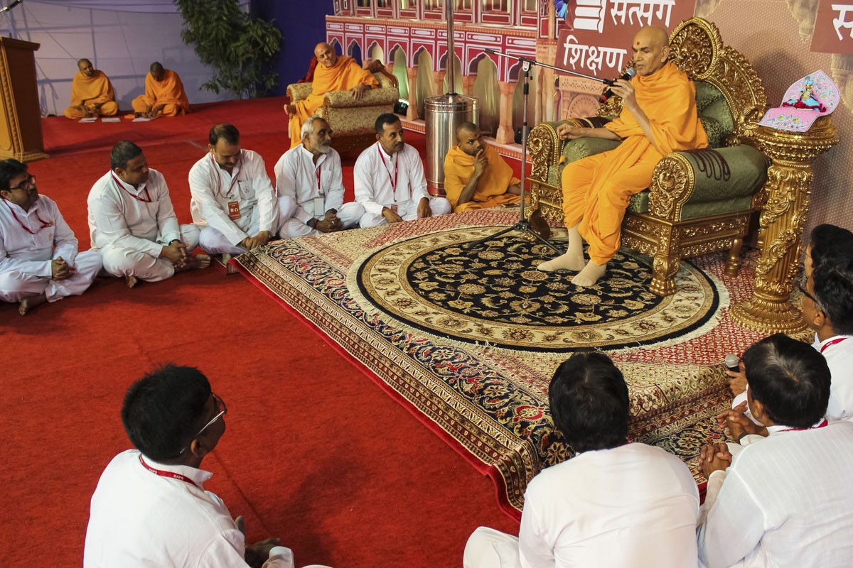 Karyakars interact with Swamishri during the evening assembly