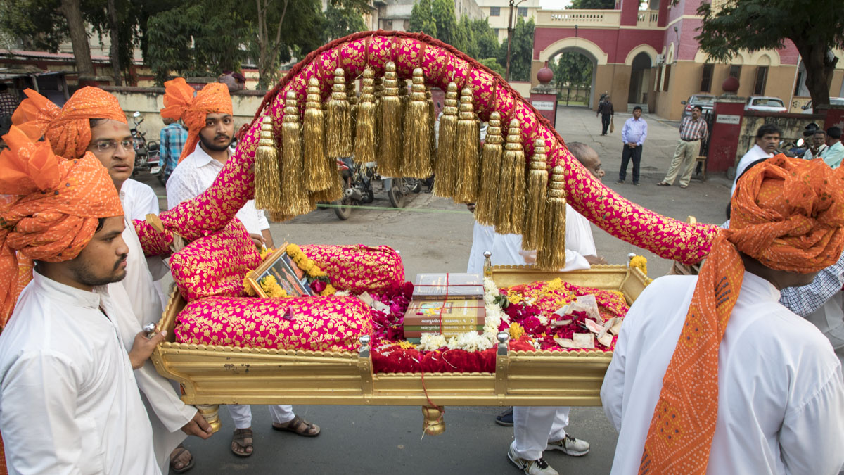 Youths carry the bhashyas in a decorated palanquin