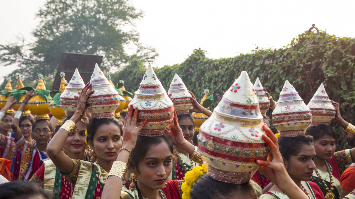 Women respectfully carry kalashes on their heads in traditional style
